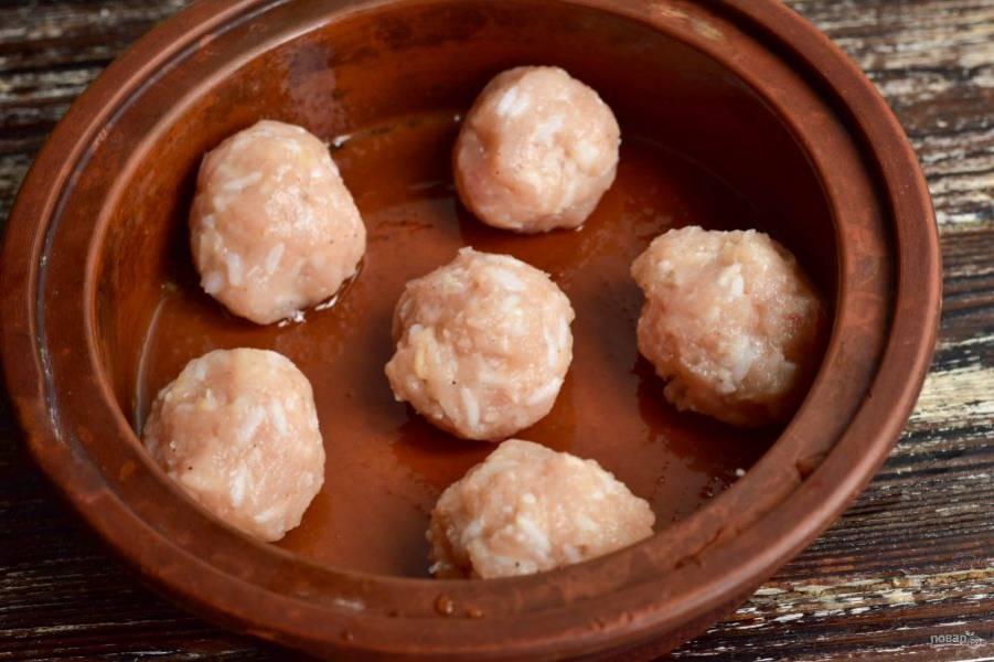 Сформируйте шарики из фарша, выложите их в форму, которую смажьте маслом. Между шариками должно быть небольшое расстояние.