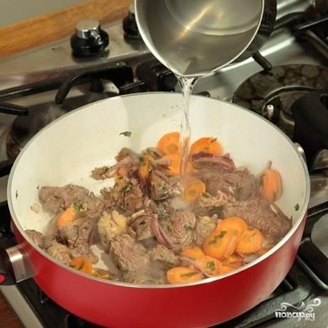 Обжарьте пару минут, после чего залейте содержимое кастрюли водой так, чтобы вода полностью покрывала ингредиенты. Тушите на среднем огне.