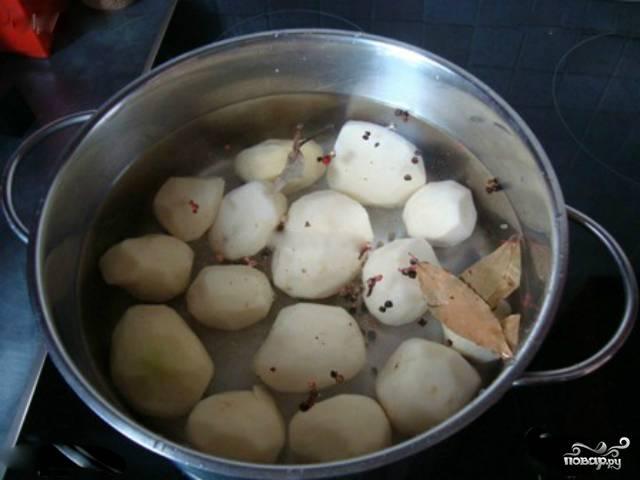 1. Картофель хорошо промойте под проточной водой, очистите от кожуры. В кастрюлю налейте воды, поставьте на средний огонь и положите в неё картошку. Добавьте лавровый лист и душистый перец горошком. Варите примерно 15 минут после закипания воды.