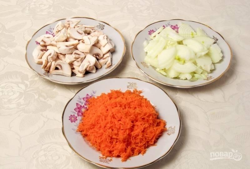 А пока займитесь другими продуктами. Морковь промойте, почистите и натрите на мелкой тёрке. Шампиньоны промойте и нарежьте пластинками. Лук очистите и нашинкуйте полукольцами.