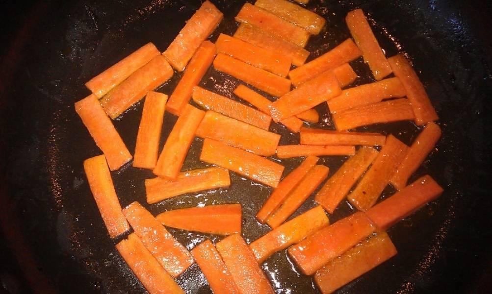 Затем обжариваем нарезанную брусочками морковь и выкладываем сверху на лук.