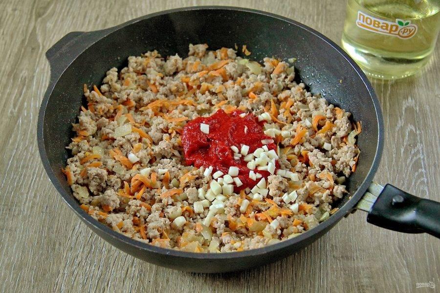 Добавьте томатную пасту и мелко нарезанный чеснок.
