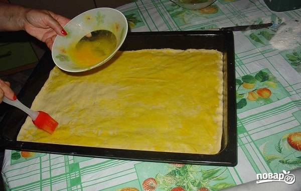 9. Затем второй пласт теста и оставшаяся начинка. Третий кусочек раскатайте и выложите сверху. Взбейте вилкой желтки и смажьте с помощью кисточки поверхность, чтобы пахлава была румяной.