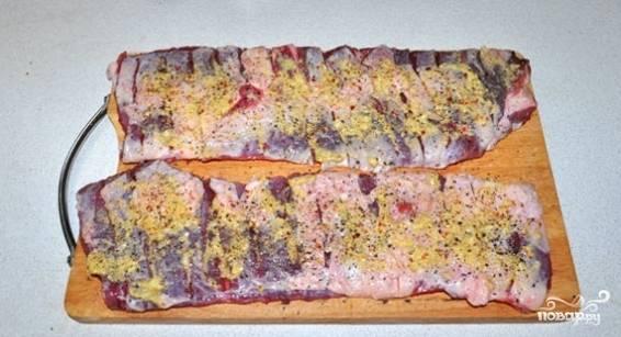 При помощи хорошо заточенного ножа, сделайте на брюшине насечки таким образом, чтоб рассечь пленку с жиром. Натрите смесью перцев, солью и толченым чесноком. Сверните два рулета, так как один будет слишком долго пропекаться.