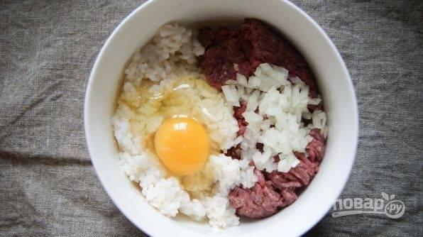 Теперь в фарш добавьте соль, специи и рубленный лук, а также промытый рис и яйцо. Хорошо перемешайте фарш.