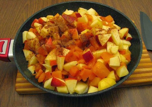 4. Яблоки нарежьте также кубиками (в данном случае шкурка тонкая, и срезать ее необязательно) и добавьте на сковороду. Жарьте до мягкости, периодически помешивая. За 2 минуты до готовности всыпьте корицу и еще раз перемешайте. При желании дополнить этот простой рецепт пирога с тыквой и яблоками можно ароматными травами, например.