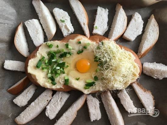 5. На застеленный пергаментом противень выложите батон и наполните его картофельным пюре.  В центре сделайте углубление и вбейте яйцо. Посыпьте зеленью и сыром, не попадая на желток.