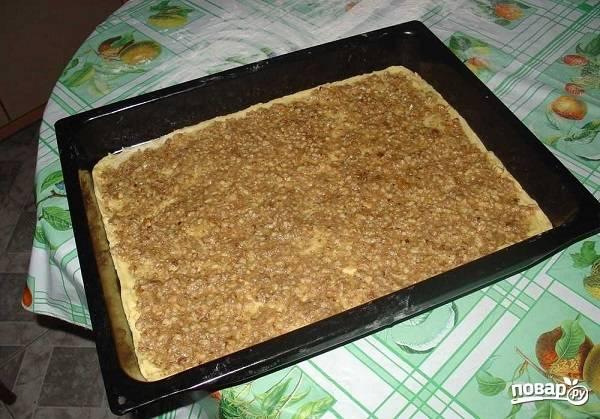 8. На тесто выложите примерно половину ореховой начинки.
