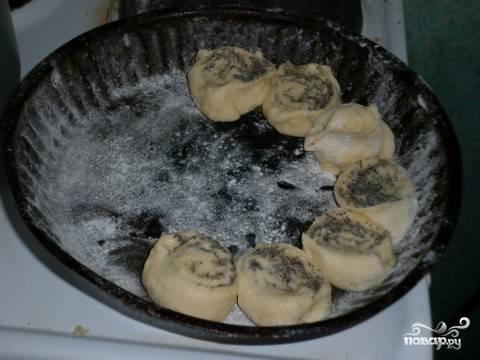 5. Жаропрочную форму смажьте немного маслом и присыпьте мукой. Выложите булочки. Повторите процесс со второй половиной теста.