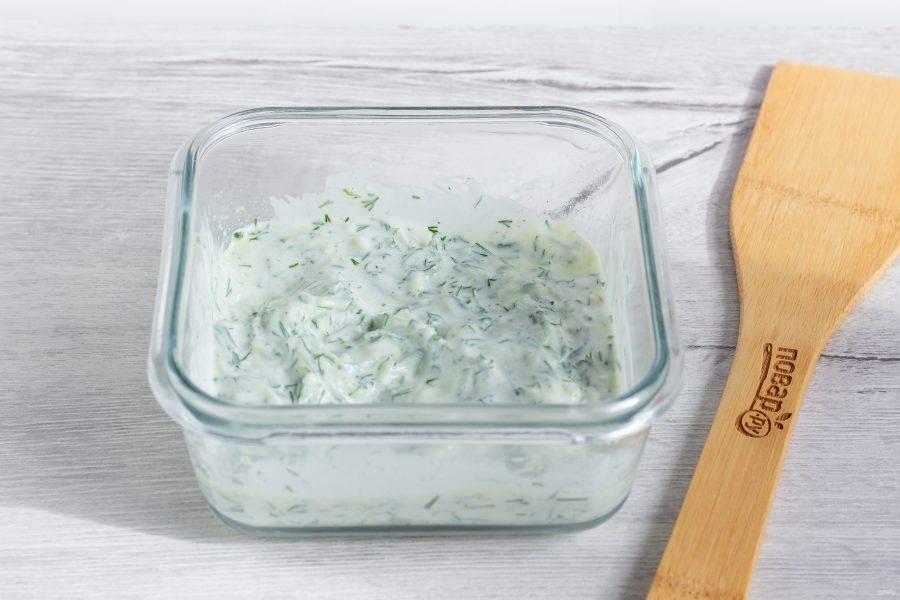 В йогурт добавьте мелко рубленный чеснок и укроп, 1 ч. л. оливкового масла, огурец. Всё хорошо перемешайте. Посолите и поперчите по вкусу.