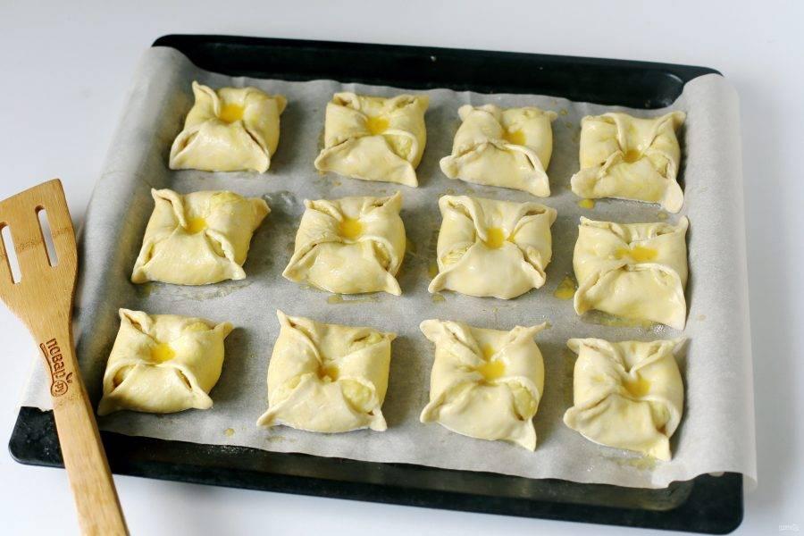 Переложите заготовки на противень, застеленный пекарской бумагой и смажьте взбитым яйцом. Готовьте в духовке при температуре 180 градусов около 20-25 минут.