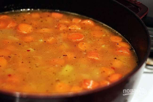 2. Влейте бульон и оставьте вариться под крышкой на полчаса.  Тем временем соедините фарш с тертым сыром и панировочными сухарями. Добавьте специи и соль.