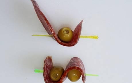 3. Теперь накалываем кусочек салями сбоку, оливку, и закрепляем второй стороной салями, как на фото.