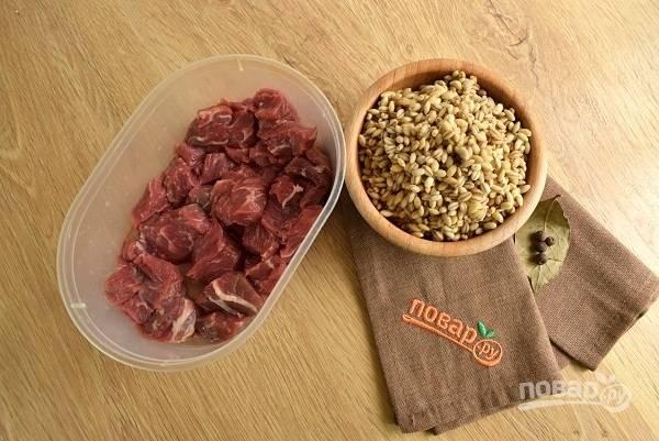 Подготовьте мясо и перловую крупу.  Крупу промойте прохладной водой. Залейте кипятком. Мясо промойте прохладной водой, нарежьте средними кубиками.