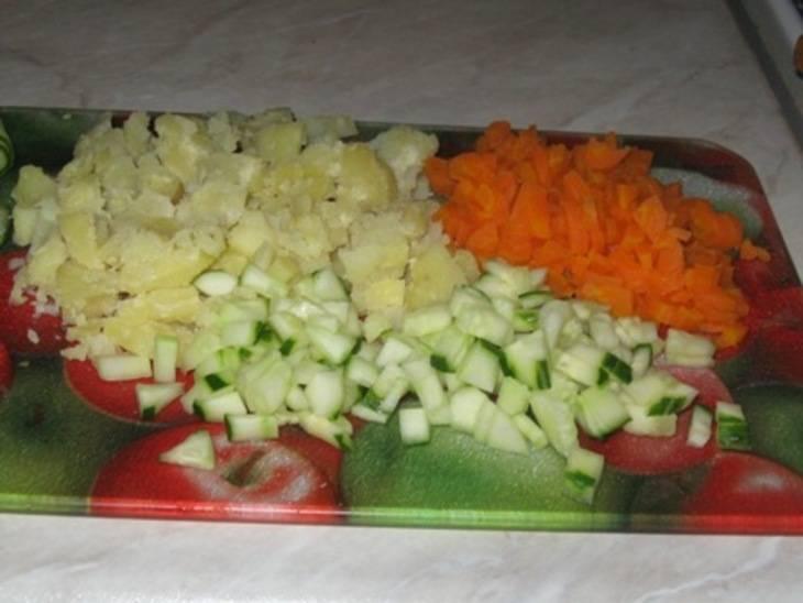 2. Нарежьте кубиками огурцы,  морковь и картофель. На крупной терке натрите яблоко или порежьте мелкой соломкой. Листья салата также  измельчите.