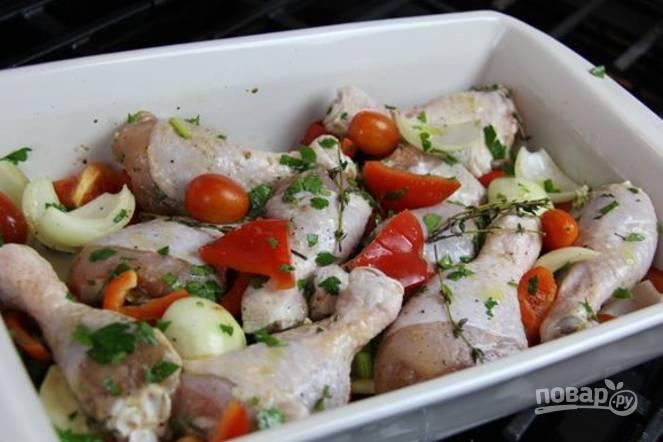 В форму для запекания выложите ножки, налейте масло, добавьте соус, соль и перец, добавьте петрушку, измельченный имбирь и чеснок, овощи. Все хорошенько перемешайте руками. Положите тимьян.