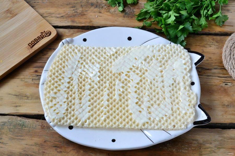 Вафельные коржи я слегка обрезала, чтобы сделать их слегка прямоугольными. Первый корж положите на плоскую тарелку и смажьте майонезом.