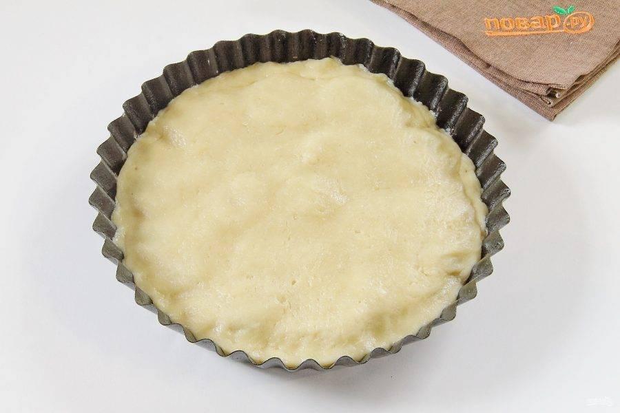 Достаньте тесто и раскатайте его в форме круга по размеру чуть больше формы. Накройте тестом начинку и подверните внутрь края.