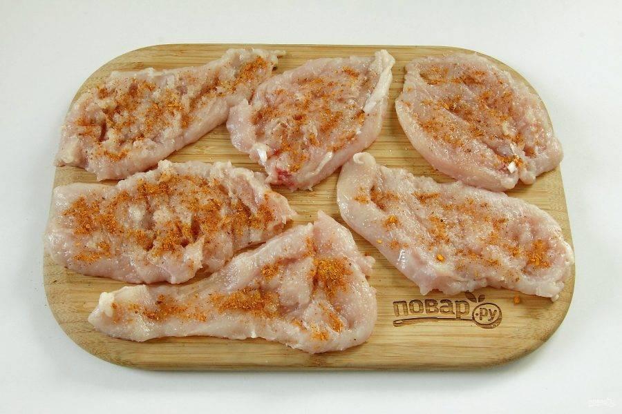 2. Куриное филе разрежьте вдоль на три части. Каждую часть отбейте специальным молоточком, посолите и поперчите по вкусу.