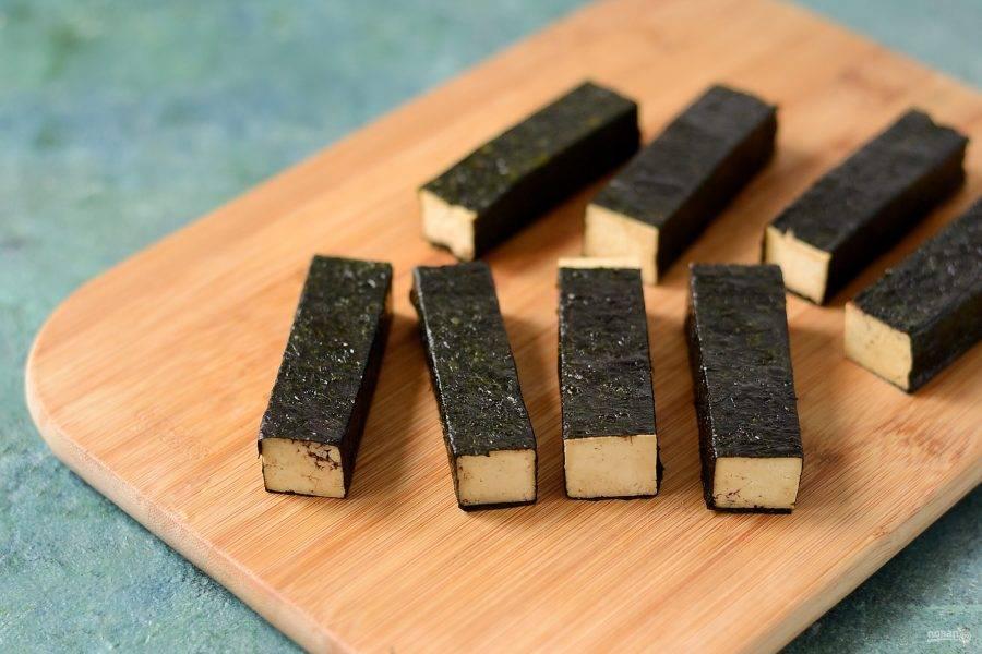 Смажьте водоросли соевым соусом, дайте им пару секунд размягчиться. Затем оберните тофу в нори. Плотно прижмите размоченные водоросли, чтобы они лучше держались.