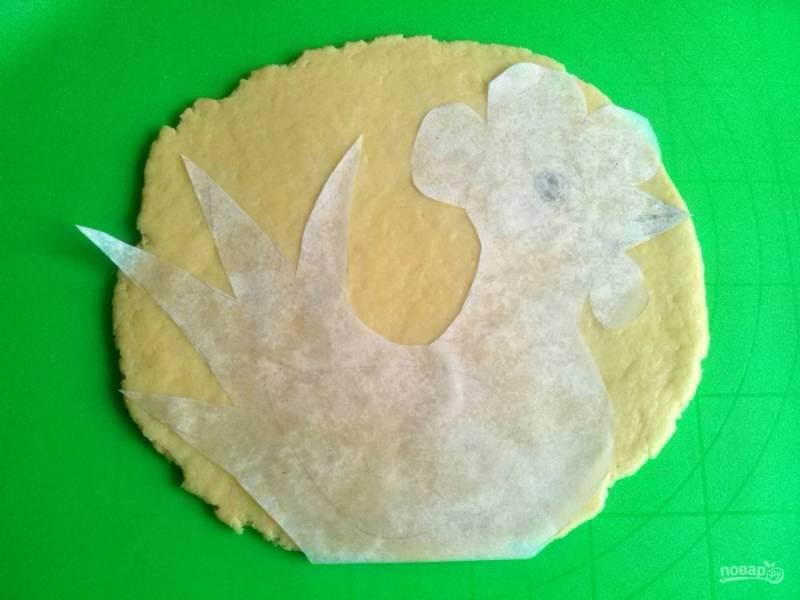 Разделите тесто на две части, раскатайте каждую в лепешку толщиной 0,5 см. Приложите к лепешке шаблон петуха из пергамента, вырежьте фигуру острым ножом. Также поступите и со второй лепешкой теста. Переложите заготовку на пергамент.