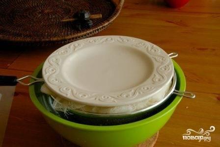 Разравниваем и закрываем краями марли творожную массу. Наверх ставим тарелку, а на — нее груз. И ставим блюдо в холодильник минимум на 12 часов, максимум - на сутки.