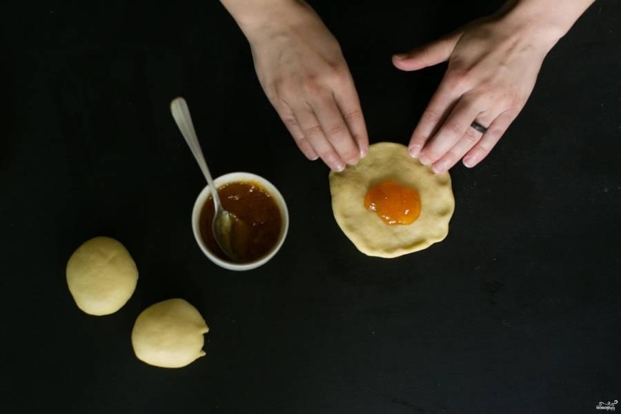 Положите по чайной ложке джема и плотно залепите, сформировав круглый шарик. Джем не должен вытечь.