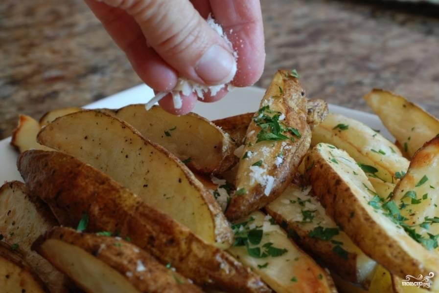 Готовый картофель достаем из духовки, посыпаем свежей петрушкой и мелко тертым пармезаном.