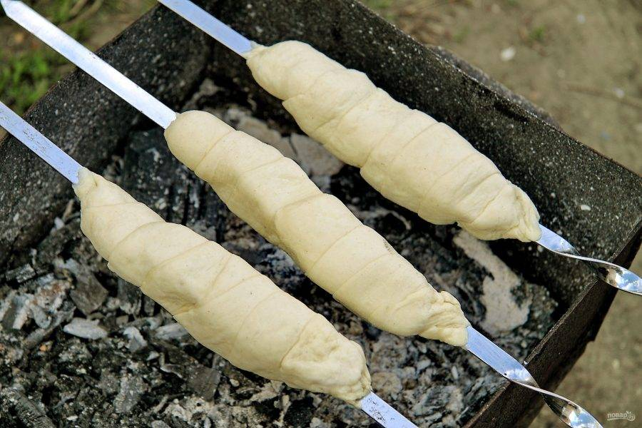Заверните сыр в тесто, тщательно закрепляя края. Обжарьте слоеные хачапури на очень слабых углях, до равномерной корочки.