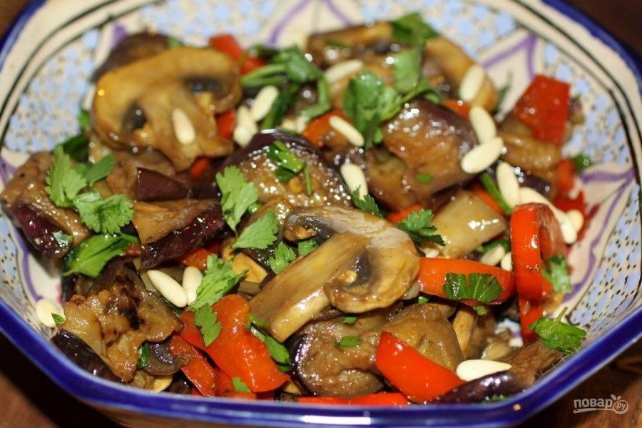 4. Смешиваем обжаренные овощи и грибы, добавляем зелень и соль по вкусу. Теперь нам нужно добавить уксус (желательно бальзамический). Все перемешиваем, выкладываем в порционную емкость и посыпаем кедровыми орешками. Такой салат из баклажана можно подавать даже теплым.