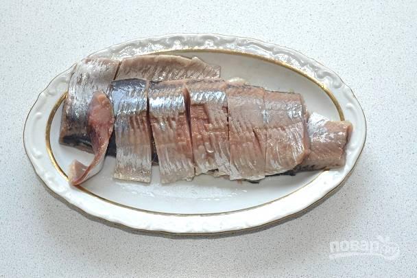 Селедку очистите, аккуратно отделите филе и нарежьте небольшими ломтиками.