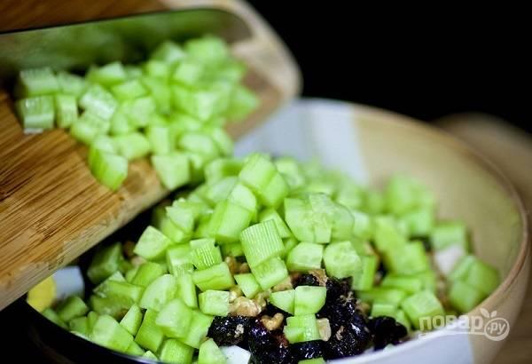 6. Огурцы вымойте, при желании очистите и нарежьте их кубиками. Добавьте в салат.