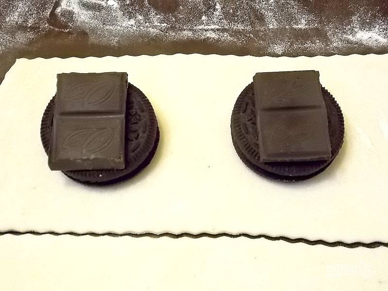 Уложите на расстоянии печенье, сверху положите кусочки шоколада.