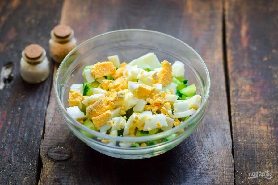 Куриное яйцо отварите вкрутую, почистите и нарежьте небольшими кубиками, добавьте в салат.