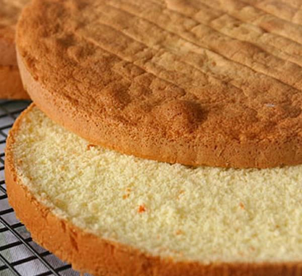 2. Выпекайте бисквит при температуре около 180 градусов до румяности. Затем дайте ему немного остыть, переложите на решетку и полностью охладите. Острым ножом разрежьте корж пополам.