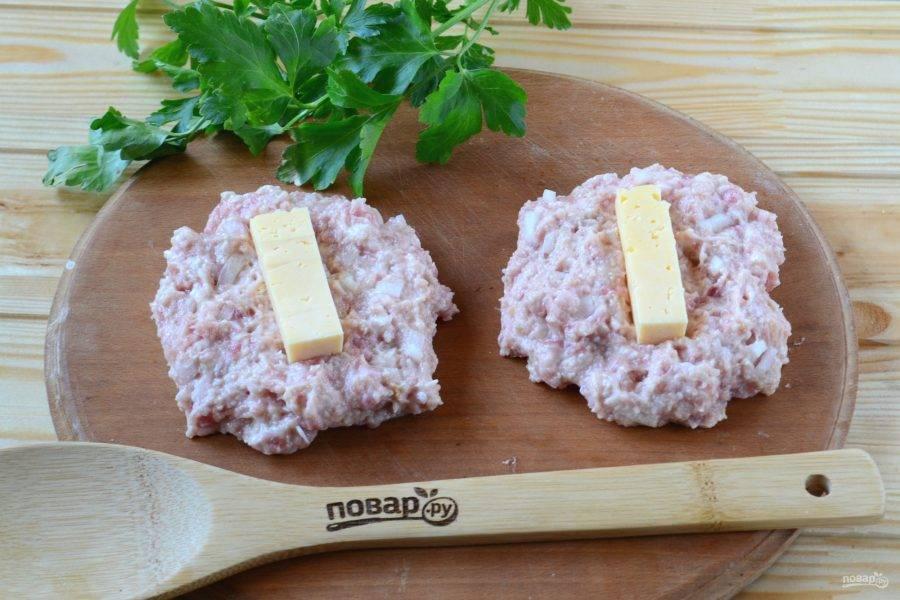 Из готового фарша сформируйте лепешки с половину ладони. На лепешку положите брусочек твердого сыра и сформируйте овальную продолговатую котлету.