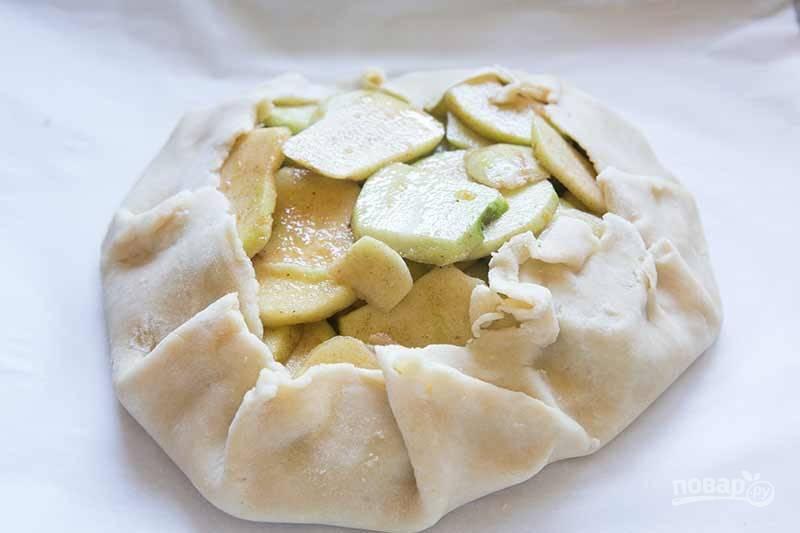 6.Аккуратно поднимите и задрапируйте края теста над яблоками. Взбейте вместе яичный белок и 1 чайную ложку сливок, нанесите кисточкой эту смесь на края теста. Посыпьте 1 чайной ложкой сахара открытые яблоки, смажьте оставшимся сливочным маслом.