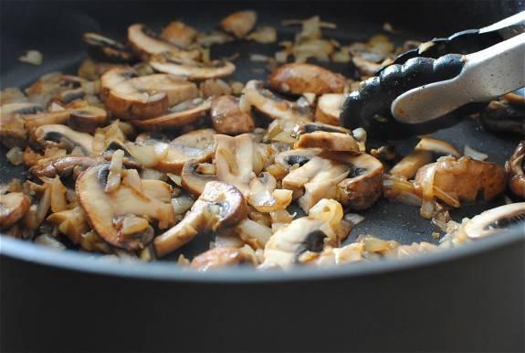 3. На отдельную сковороду налить немного растительного масла и поставить на огонь. Тем временем очистить луковицу и нарезать мелкими кубиками. Отправить лук на сковороду и обжарить до прозрачности. Пока лук жарится, вымыть, просушить и нарезать грибы. Отправить грибы на сковороду с луком и жарить до золотистой корочки.