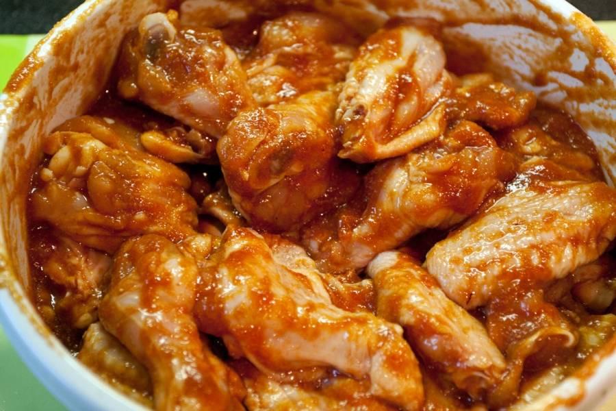 В отдельной посуде смешиваем соевый соус, кетчуп, сахар, чесночный порошок и чили, солим. Выкладываем эту массу к курице и перемешиваем все, чтобы соус равномерно распределился по крылышкам. Накрываем миску полотенцем и оставляем крылышки мариноваться на 15 минут.