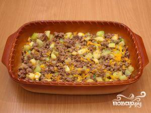 Форму для выпекания немножко смазываем маслом, выкладываем в нее кабачки и мясной фарш. Разравниваем.