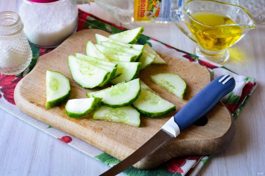 Вымойте огурцы, срежьте хвостики и нарежьте полукольцами для салата.