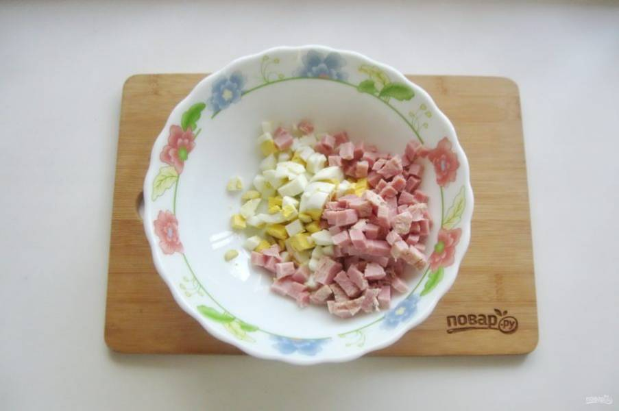 Ветчину нарежьте кубиками и добавьте к яйцам.