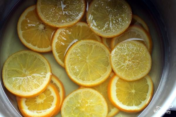 1. Вымойте и нарежьте апельсины тонкими дольками. 150 грамм сахара размешайте в 350 мл. воды. Дольки апельсина сложите в сотейник с водой, сахаром и поставьте на плиту. Варить нужно до тех пор, пока кожура апельсина не станет мягкой.