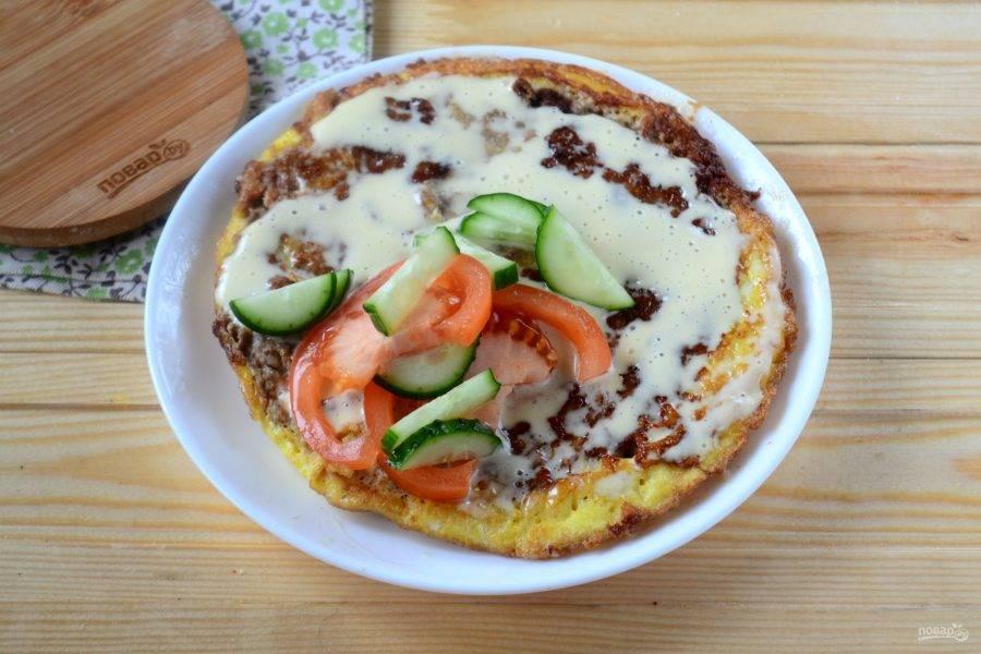 Готовый блин положите яйцом вниз. Фарш смажьте майонезом или любимым соусом, положите нарезанные огурец и помидор. Также можно положить кусочки сладкого перца, красный лук и т. д.