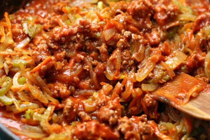 Добавьте к мясу обжаренные овощи, а также специи. Готовьте все вместе на медленном огне под крышкой (примерно 1 час). Время от времени помешивайте.