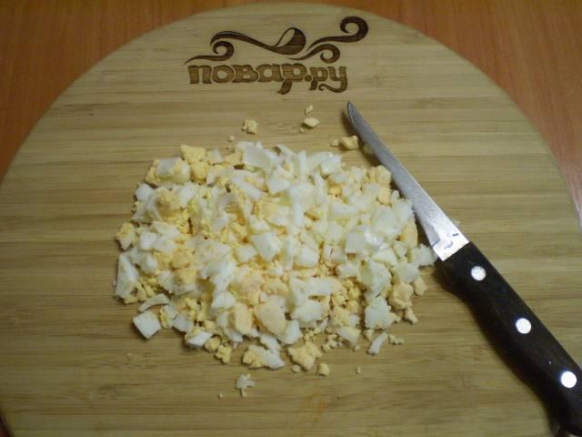 Отварные яйца чистим, рубим ножом на кубики.