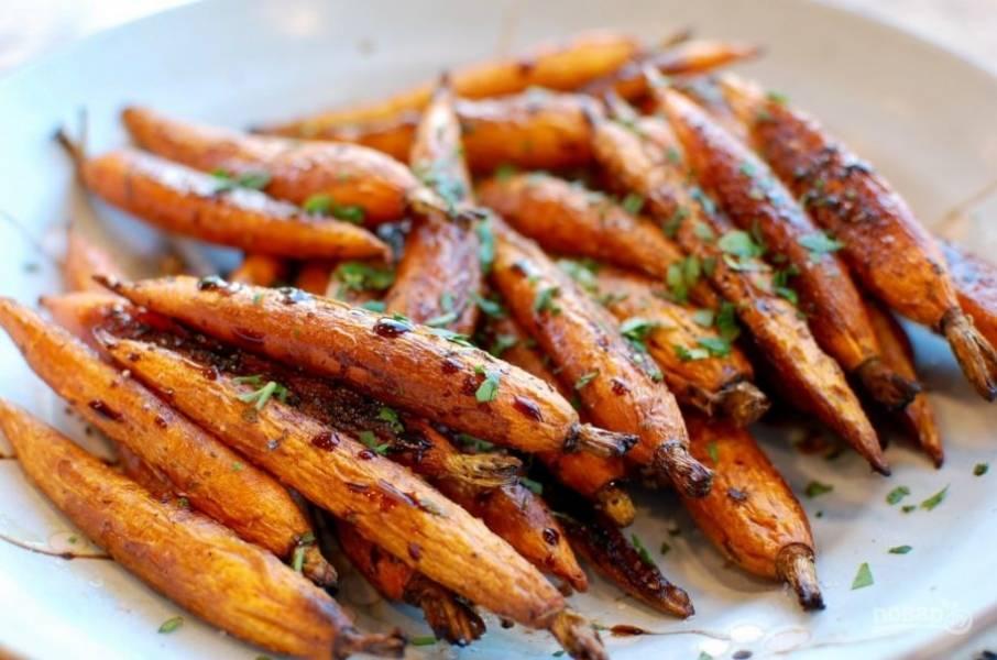 7.Затем достаньте морковь, переверните ее и снова поставьте в духовку на 20 минут. Приготовленную морковь достаньте, посыпьте петрушкой и подавайте к столу.