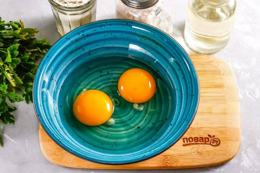 В глубокую емкость вбейте куриные яйца, всыпьте соль и взбейте яйца венчиком примерно 2-3 минуты.