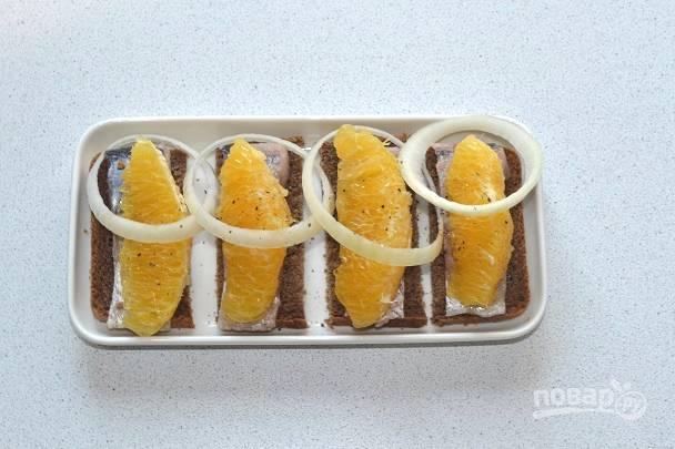 Сверху выложите ломтик апельсина, дополните кружочком лука и присыпьте молотым перцем.