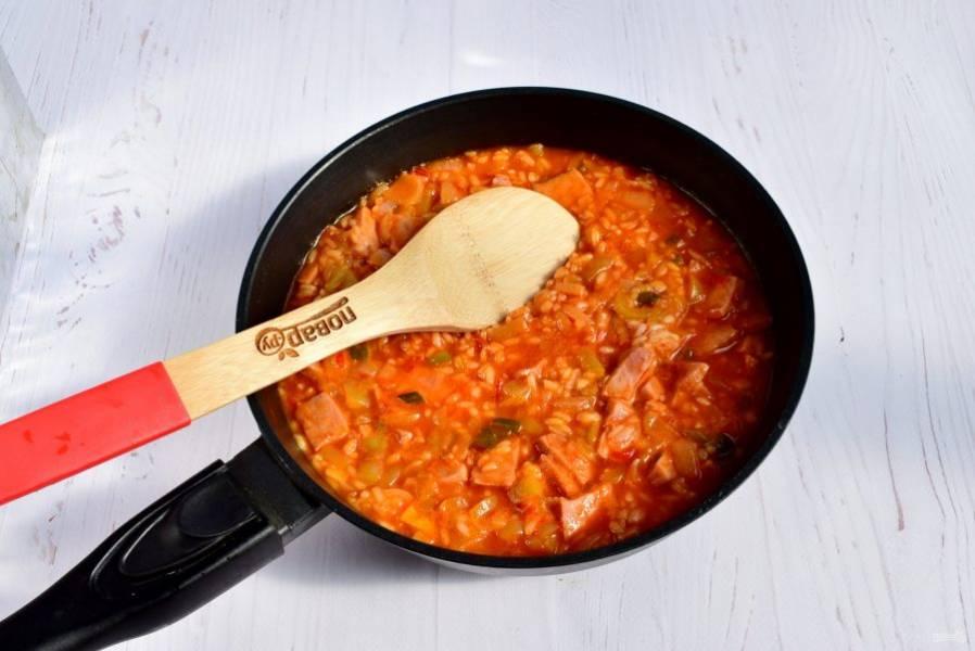 Добавьте рис, воду (или мясной бульон), доведите до кипения, накройте крышкой. На медленном огне готовьте в течение 20-25 минут до готовности риса.